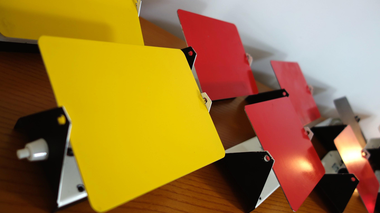 Charlotte PERRIAND (1903-1999) Ensemble de 6 appliques « CP1″ – 1962 Réflecteurs en métal laqué émaillé rouge, jaune et noir; base en métal blanc. Provenance station des Arcs, étiquette SCE, circa 1970. Ht: 12,5cm, l: 17cm p: 7cm